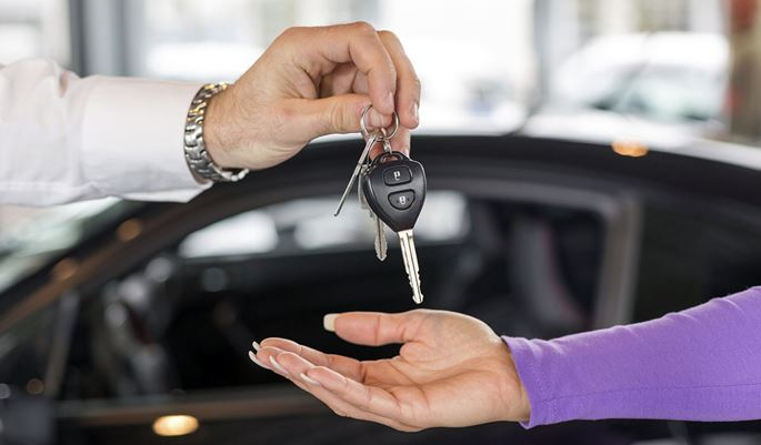 Salesman handing over car keys in dealership
